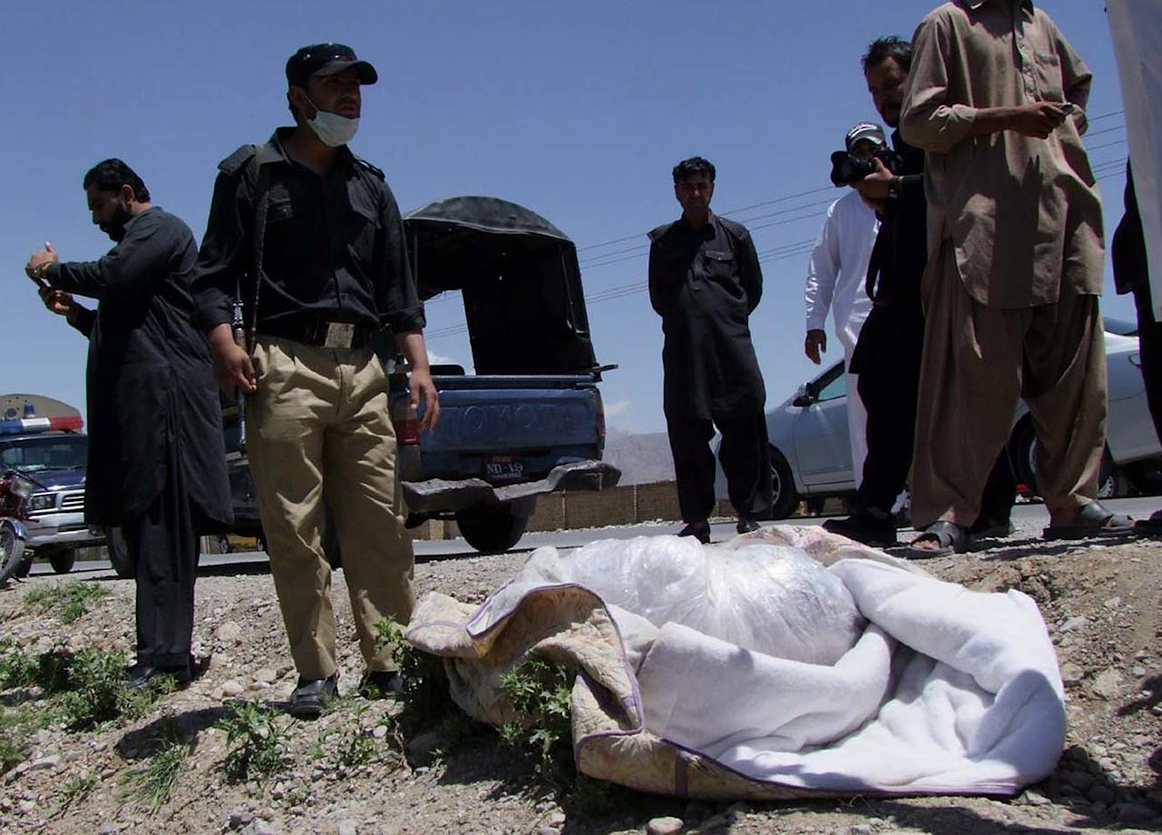 Pakistani security officials stand next to covered body of British Red Cross worker Khalil Rasjed Dale at the site in Quetta, Pakistan on Sunday, April 29, 2012. The body of a British Red Cross worker held captive in Pakistan since January was found in an orchard Sunday, his throat slit and a note attached to his body saying he was killed because no ransom was paid, police said. (AP Photo/Arshad Butt)
