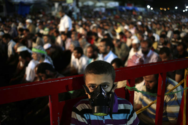 A boy wears a tear gas mask as supporters of Egypt's ousted President Mohammed Morsi pray at Nasr City, where protesters have installed a camp and hold daily rallies, in Cairo, Egypt, Sunday, July 28, 2013. Deadly clashes broke out during funerals of slain supporters of Egypt's ousted Islamist president Sunday, as the supreme leader of the Muslim Brotherhood urged his followers to stand fast after more than 80 of them were killed in weekend violence. (AP Photo/Hassan Ammar)