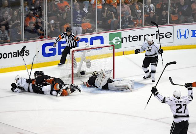 Anaheim Ducks defenseman Cam Fowler, third from left, and defenseman Sami Vatanen, of Finland, second from left, lie on Los Angeles Kings right wing Justin Williams, left, who scored on Anaheim Ducks goalie John Gibson, center, as Kings center Mike Richards, upper right, and defenseman Alec Martinez, lower right, celebrate during the first period in Game 7 of an NHL hockey second-round Stanley Cup playoff series, Friday, May 16, 2014, in Anaheim, Calif. (AP Photo/Mark J. Terrill)