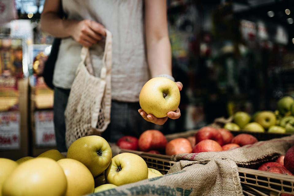 Close up of young woman shopping for fresh organic fruits in farmer's market with a cotton mesh eco bag.