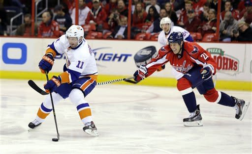 New York Islanders defenseman Lubomir Visnovsky (11), from Slovakia, looks to pass as Washington Capitals center Brooks Laich (21) reaches to defend during the first period of an NHL hockey game Tuesday, March 26, 2013, in Washington. (AP Photo/Alex Brandon)