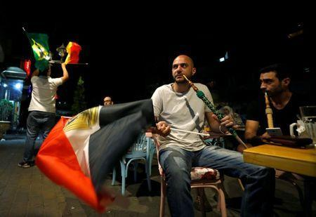 A man holds the Egyptian flag as he watches the World Cup 2018 match between Egypt and Russia, at a cafe in Damascus, Syria June 19, 2018. Picture taken June 19, 2018. REUTERS/Omar Sanadiki