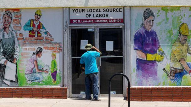 PHOTO: A person looks inside the closed doors of the Pasadena Community Job Center in Pasadena, Calif., May 7,2020. (Damian Dovarganes/AP, FILE)
