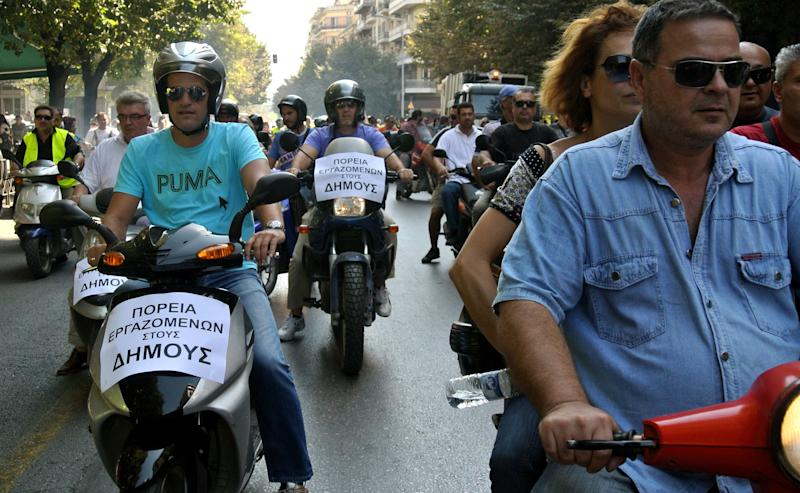 "Municipal workers drive their motorcycles during a protest against the new austerity measures in the northern port city of Thessaloniki, Greece, on Wednesday, Oct. 3, 2012. Greece's brutal recession is set to extend into a sixth year in 2013, when the economy will contract by another 3.8 percent, according to forecasts in the draft budget submitted to Parliament. Unemployment is predicted to rise to 24.7 percent in 2013 from an average 23.5 percent in 2012. The budget sees Greece's government still running at a loss despite waves of spending cuts and tax hikes over the past two years, as it has struggled to meet the terms for rescue loans from other eurozone countries and the International Monetary Fund. Banner reads: reads ""protest of municipality workers"". (AP Photo/Nikola Giakoumidis)"