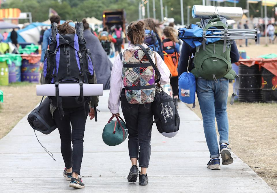 Festival goers carry tents and bags on their journey home at the 2019 Glastonbury Festival held at Worthy Farm, in Pilton, Somerset on July 1, 2019 near Glastonbury, England. The festival, founded in 1970, has grown into one of the largest outdoor green field festivals in the world. (Photo by Matt Cardy/Getty Images)