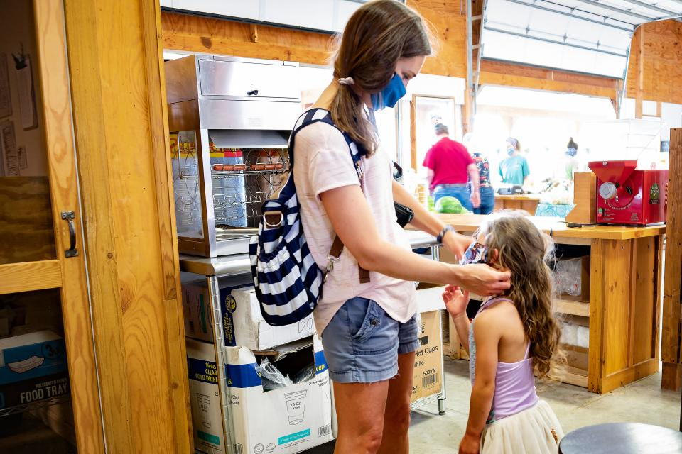 A woman adjust her daughters mask as they shop for local produce at Godfrey's Farm amid the coronavirus pandemic in Sudlersville, Maryland, on May 28, 2020. (Photo by JIM WATSON / AFP) (Photo by JIM WATSON/AFP via Getty Images)