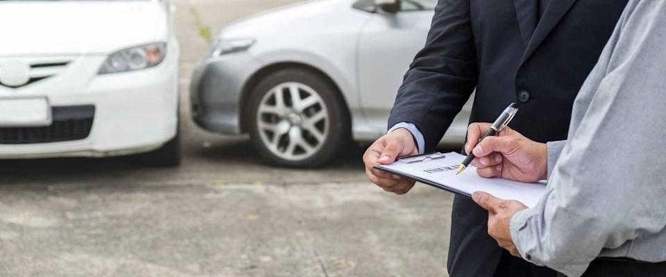 Two men holding form on a clipboard and pen with cars in the background