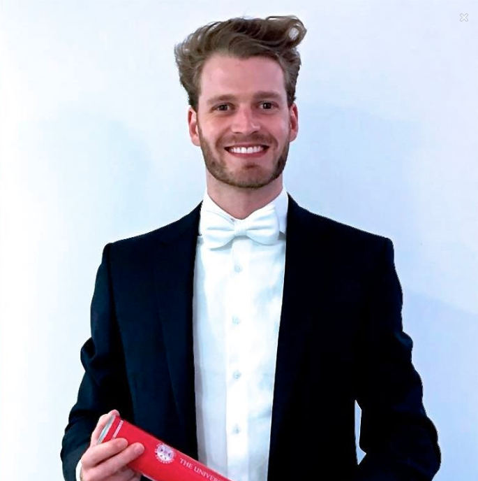 Louis, Viscount Althorp poses in a tuxedo with his degree.