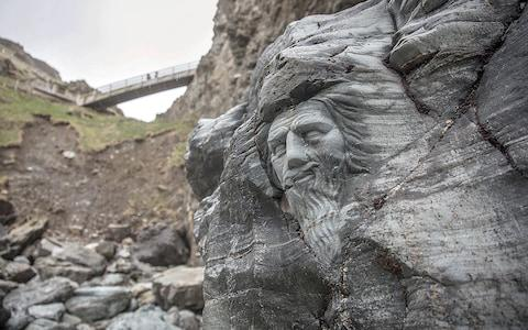 The carving at the opening of Merlin's Cave; - Credit: Getty Images
