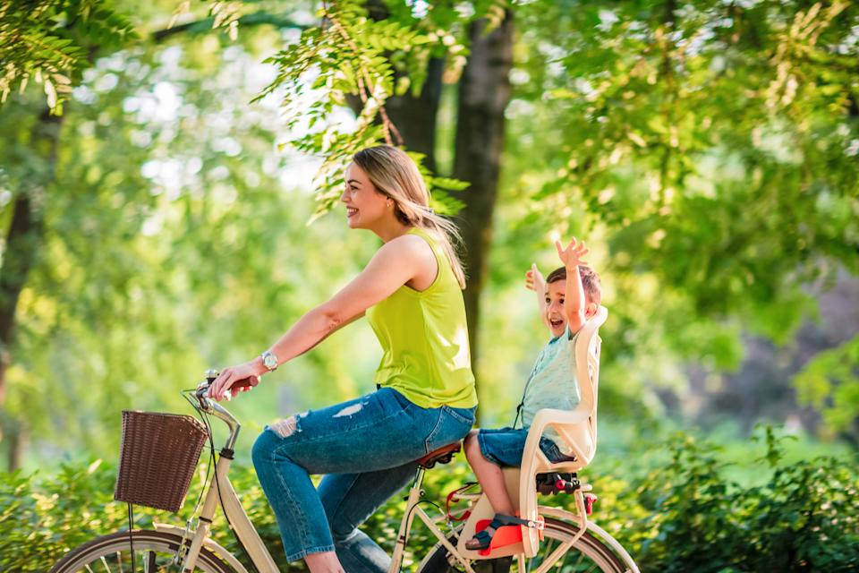 Happy family. Happy mother and son riding a bicycle together outdoors in a city park Happy mother and son on bicycles in park