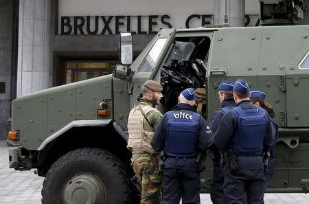 A Belgian soldier and police officers stand next to a military armoured vehicle parked at the entrance of Brussels central train station, November 22, 2015, after security was tightened in Belgium following the fatal attacks in Paris. REUTERS/Francois Lenoir