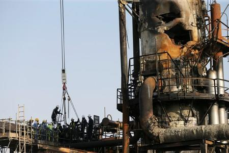 Workers are seen at the damaged site of Saudi Aramco oil facility in Abqaiq