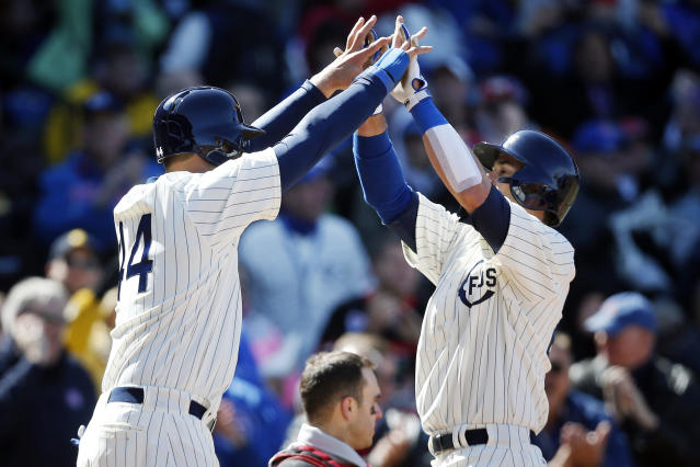 Chicago Cubs first baseman Anthony Rizzo, left, and Justin Ruggiano, right, celebrate after Rizzo scored on Ruggiano's home run during the sixth inning of a baseball game against the Arizona Diamondbacks at Wrigley Field in Chicago on Wednesday, April 23, 2014. (AP Photo/Andrew A. Nelles)