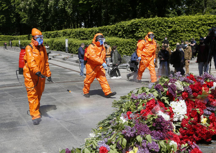 Municipal workers in special suits to protect against coronavirus disinfect an area around the monument to the Unknown Soldier in flowers at a memorial to World War II veterans in a memorial park in Kyiv, Ukraine, Saturday, May 9, 2020 on the 75th anniversary of the end of World War II. Ukraine marks the 75th anniversary of the end of World War II in Europe at a time of coronavirus lockdown and loneliness spent in search of memories both bitter and sweet. (AP Photo/Efrem Lukatsky)