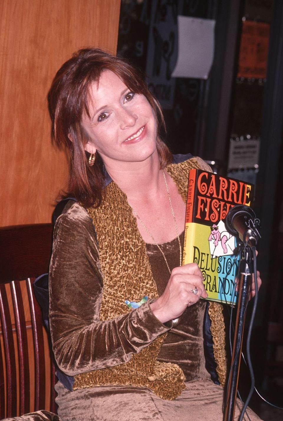 "<p>Shortly after her daughter's birth, the actress-turned-novelist churned out another best-selling novel, which was loosely based on her life. Here, Carrie is seen at a book signing for <em><a href=""https://www.amazon.com/Delusions-Grandma-Carrie-Fisher/dp/150113681X?tag=syn-yahoo-20&ascsubtag=%5Bartid%7C10055.g.32222003%5Bsrc%7Cyahoo-us"" rel=""nofollow noopener"" target=""_blank"" data-ylk=""slk:Delusions of Grandma"" class=""link rapid-noclick-resp"">Delusions of Grandma</a>, </em>which was released in 1993. </p>"