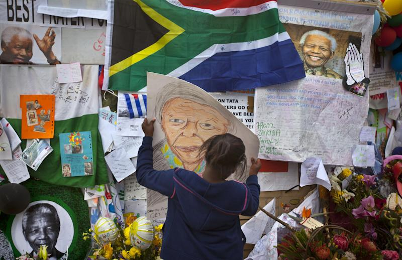 Angel Sirenje, who turned 9 Monday, places a drawing she made of Nelson Mandela on a wall of get-well messages and flowers laid outside the Mediclinic Heart Hospital where former South African President Nelson Mandela is being treated in Pretoria, South Africa, Monday, July 8, 2013. There was no official update Monday morning on the health of the 94-year-old former president and anti-apartheid leader, who was admitted June 8 to the hospital for a recurring lung infection. (AP Photo/Ben Curtis)