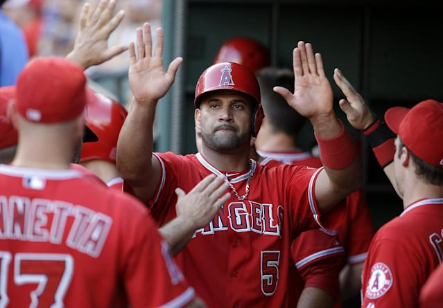 Los Angeles Angels' Albert Pujols is congratulated in the dugout after scoring on a Erick Aybar single that came off a pitch from Texas Rangers' Colby Lewis in the second inning of a baseball game, Thursday, July 10, 2014, in Arlington, Texas. (AP Photo/Tony Gutierrez)