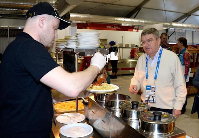 IOC President Thomas Bach waits for his lunch in the Athletes Olympic Village prior to the start of the 2014 Winter Olympics in Sochi, Russia, on Saturday, Feb. 1, 2014. (AP Photo/Pascal Le Segretain, Pool)