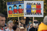 "People hold banners that read ""Let us breathe"" and ""Your fear won't take my freedom"" during a protest in Bucharest, Romania, Saturday, Sept. 19, 2020. Several hundred Romanians, including many families with young children, held a protest in the country's capital against measures meant to curb the spread of the coronavirus, especially social distancing and the mandatory use of masks in schools. (AP Photo/Vadim Ghirda)"