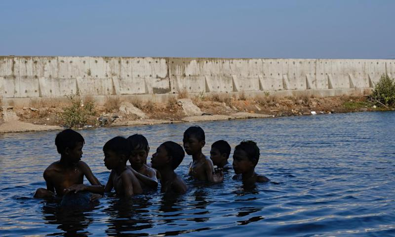 Boys swim in floodwater on the land side of a recently built seawall in Jakarta, Indonesia.