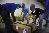 From left, Tim Williams, warehouse assistant for Medisys, Ray Fredericks, assistant director for Medisys, and Dr. Abhu Kaur with Khalsa Aid USA, a global humanitarian organization, load dozens of electrical transformers onto a pallet, which will be shipped to New Delhi with oxygen concentrators this week on New York's Long Island, Friday, May 7, 2021. With teams deployed in India to help support COVID-19 patients, Khalsa Aid USA plans to provide a total of 500 oxygen concentrators and 500 transformers to cities throughout the country. (AP Photo/Jessie Wardarski)