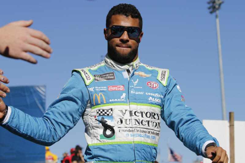 FILE - In this Oct. 27, 2019, file photo, Bubba Wallace greets fans during a NASCAR Cup Series race at Martinsville Speedway in Martinsville, Va. Bubba Wallace, the only African-American driver in the top tier of NASCAR, calls for a ban on the Confederate flag in the sport that is deeply rooted in the South. (AP Photo/Steve Helber, File)