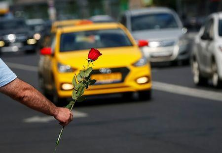 A man waits for customers as he sells flowers by a street in central Moscow, Russia June 29, 2018. REUTERS/Gleb Garanich