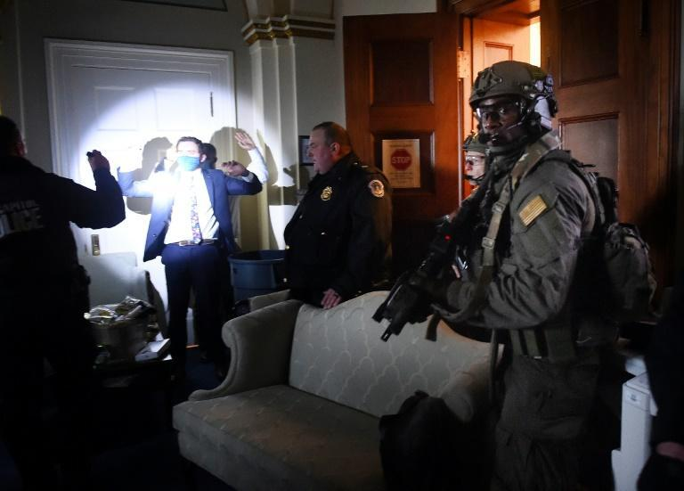 Congress staffers hold up their hands while Capitol Police SWAT teams secure the US legislature after it was stormed by right-wing protestors.