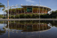 A venue at Olympic Park is reflected in a pool of water in the Barra da Tijuca western zone of Rio de Janeiro, Brazil, Thursday, June 24, 2021. With the Olympics about to kick off in Tokyo, the prior host is struggling to make good on legacy promises with Rio de Janeiro's Olympic Park venues mostly unused. (AP Photo/Bruna Prado)