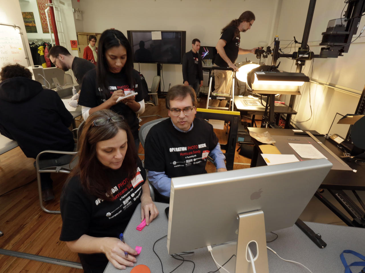 In this Saturday, Feb. 2, 2013 photo, Scott Geffert, seated center, senior imaging systems manager of New York's Metropolitan Museum of Art, assisted by Sharron Diedrichs, left, and Diana Mathura, catalog photos accepted for restoration by Operation Photo Rescue-Hurricane Sandy, at New York's School of Visual Arts. Of all the pictures of Superstorm Sandy's destruction, some of the most lingering are the warped, stained ones that sat on the walls and shelves of flooded homes. The Sandy project promises to be one of Operation Photo Rescue's most expert and ambitious efforts yet. (AP Photo/Richard Drew)