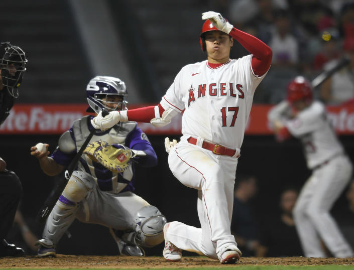 Colorado Rockies catcher Elias Diaz throws the ball back to the pitcher after Los Angeles Angels' Shohei Ohtani swung at a pitch during the fourth inning of a baseball game against Wednesday, July 28, 2021, in Anaheim, Calif. (AP Photo/John McCoy)