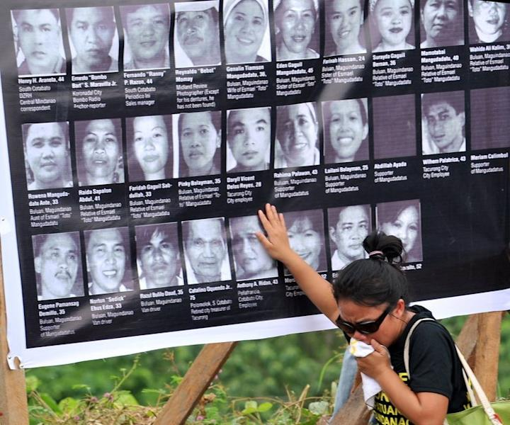 This file photo shows a relative of one of the 57 victims of the November 23, 2009 massacre crying as she touches a collage of photos of the victims during a memorial service at the massacre site in Ampatuan, Maguindanao province on the southern island of Mindanao, on November 23, 2010. The killing was the country's worst political massacre