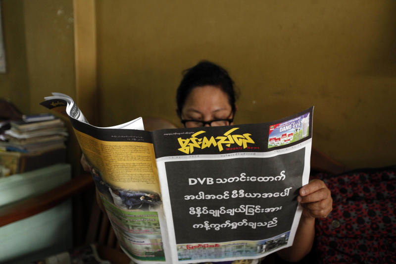 "A woman reads a local weekly news journals with its front page printed black with letters saying ""By opposing recent arrest and sentencing of journalists including a video journalist of DVB (Democratic Voice of Burma)"" Friday, April 11, 2014, in Yangon, Myanmar. Several private newspapers in Myanmar printed black front pages on Friday to protest the recent arrests and sentencing of journalists, in the latest sign the country's media climate is worsening. (AP Photo/Khin Maung Win)"