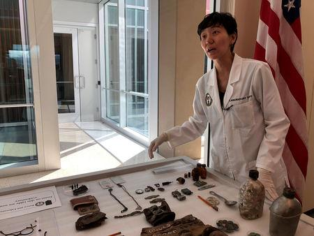 Jennie Jin shows some of the objects that accompanied the human remains handed over by North Korea at Joint Base Pearl Harbor-Hickam
