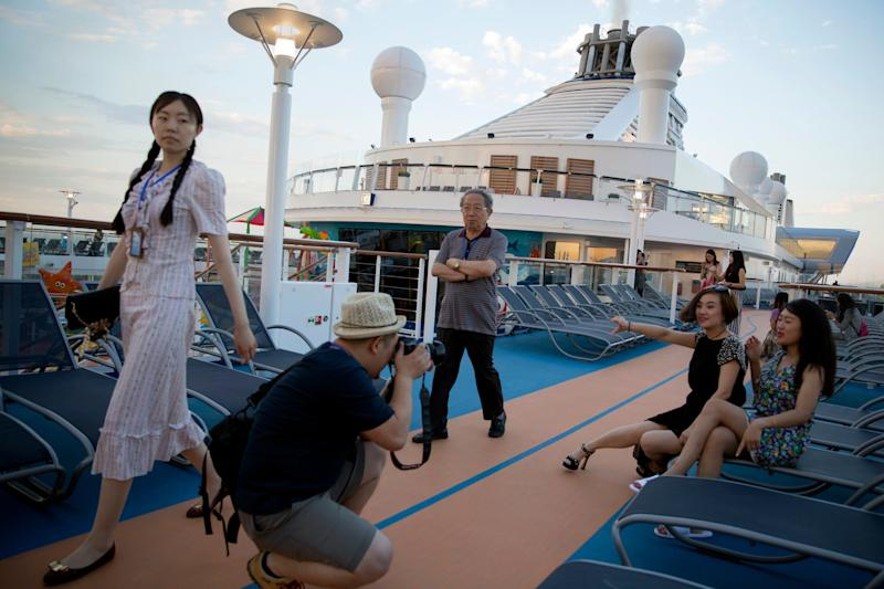 Passengers pose for photos onboard Royal Caribbean's cruise ship the Ovation of the Seas ahead of its inaugural voyage at the International Cruise Terminal in northeastern China's Tianjin Municipality, Friday, June 24, 2016. (AP Photo/Ng Han Guan)