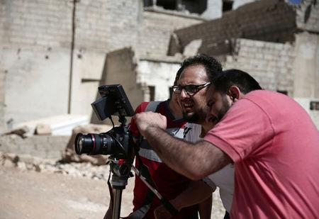 Syrian director Humam Husari (R) and cameraman Sami al-Shami (C) operate a camera as they film a scene  in the rebel-held besieged town of Zamalka, in the Damascus suburbs, Syria September 19, 2016. REUTERS/Bassam Khabieh