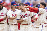 Philadelphia Phillies' J.T. Realmuto, center, is congratulated after hitting the winning home run in the 10th inning of a baseball game against the Miami Marlins, Sunday, July 18, 2021, in Philadelphia. It was a continuation of the previous day's game which was suspended due to rain. (AP Photo/Laurence Kesterson)