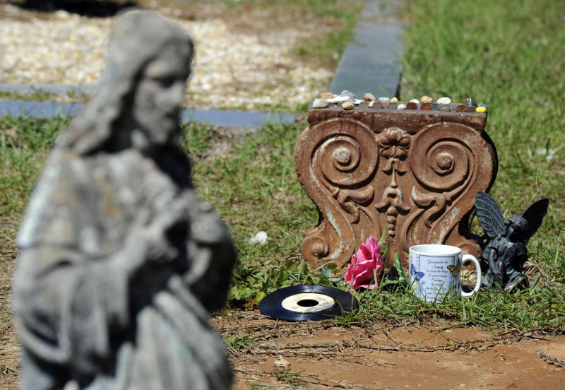 """FILE - In this photo taken Wednesday, May 3, 2017, is a statue of Jesus near the grave of John B. McLemore, who is featured in the serialized podcast """"S-Town,"""" in Green Pond, Ala. A lawsuit against the makers of the hit podcast """"S-Town"""" has been dismissed after a settlement with the late protagonist's estate. WIAT-TV reported Tuesday, May 19, 2020, that the suit filed by the estate of John B. McLemore was dismissed March 12. Details of what the settlement entailed were not disclosed. (AP Photo/Jay Reeves, File)"""