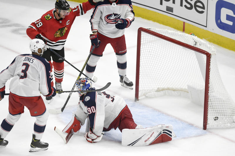 Chicago Blackhawks' Jonathan Toews (19) watches his goal against Columbus Blue Jackets goalie Elvis Merzlikins (90) of Latvia, Pierre-Luc Dubois (18) and Seth Jones (3) in overtime to win an NHL hockey game Friday, Oct 18, 2019, in Chicago. (AP Photo/Paul Beaty)