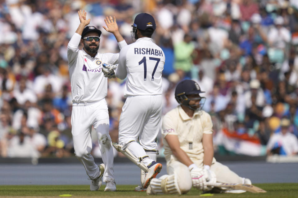 India's Virat Kohli, left, celebrates as England's Dawid Malan, right, is run out on day five of the fourth Test match at The Oval cricket ground in London, Monday, Sept. 6, 2021. (AP Photo/Kirsty Wigglesworth)