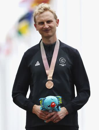 Cycling - Gold Coast 2018 Commonwealth Games - Men's Individual Time Trial - Currumbin Beachfront - Gold Coast, Australia - April 10, 2018. Bronze medallist Hamish Bond of New Zealand poses with his medal and Borobi plush doll. REUTERS/Athit Perawongmetha