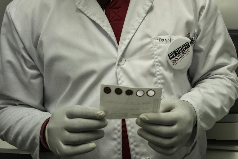 A lab technician holds blood samples inside the viral load room at a Malawi hospital in 2014