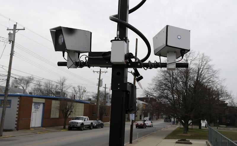 FILE - This Wednesday, Jan. 16, 2013 file photo shows a pair of traffic cameras aimed on Vine Street, in Elmwood Place, Ohio. The village was on pace to assess $2 million in traffic fines in six months until a lawsuit brought a ruling from a judge forcing the village to stop using the cameras. The village is appealing the ruling. (AP Photo/Al Behrman, File)