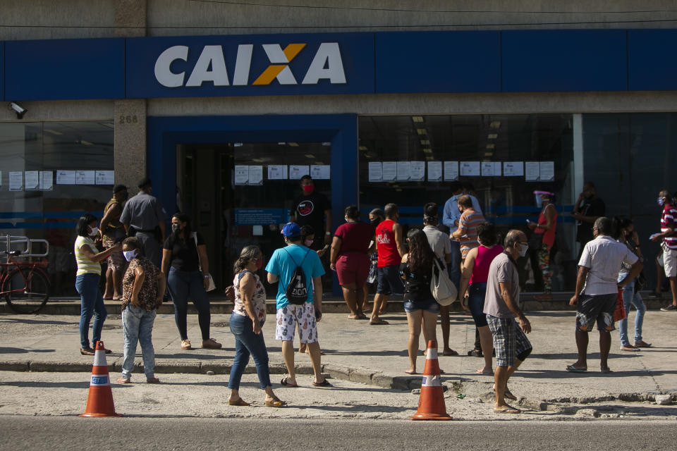 RIO DE JANEIRO, BRAZIL - MAY 18: People wearing protective masks wait in line while respecting social distancing rules outside a Caixa Economica Federal bank branch in Campo Grande neighborhood to receive the second installment of the urgent government benefit amidst the coronavirus (COVID-19) pandemic on May 18, 2020 in Rio de Janeiro, Brazil. The benefit is directed at informal workers, small individual business owners, self-employed workers, and unemployed people under vulnerability, and it has been granted as part of the efforts to tackle the coronavirus (COVID-19) pandemic. According to city hall, Campo Grande is the neighborhood with the second highest number of deaths by coronavirus (COVID-19) in the city. (Photo by Bruna Prado/Getty Images)