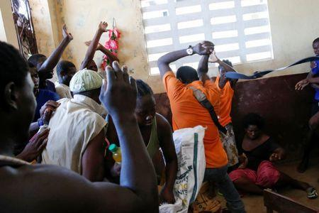 People fight as they try to get food during a special distribution in a church after Hurricane Matthew passed through Jeremie, Haiti, October 11, 2016. REUTERS/Carlos Garcia Rawlins