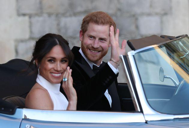 Britain's Prince Harry, Duke of Sussex, (R) and Meghan Markle, Duchess of Sussex, (L) leave Windsor Castle in Windsor on May 19, 2018 in an E-Type Jaguar after their wedding to attend an evening reception at Frogmore House. (Photo by Steve Parsons / POOL / AFP) (Photo credit should read STEVE PARSONS/AFP via Getty Images)