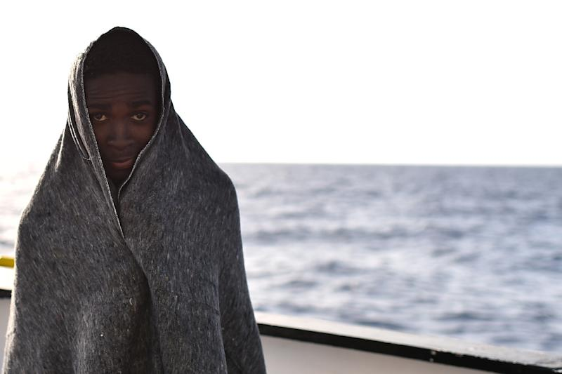 A young man stands wrapped in a blanket after a rescue operation on May 24, 2016