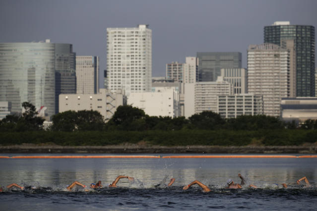 """FILE - In this Aug. 11, 2019, file photo, athletes compete in a marathon swimming test event at Odaiba Marine Park, a venue for marathon swimming and triathlon at the Tokyo 2020 Olympics, in Tokyo. The IOC moved next year's Tokyo Olympic marathons and race walks out of the Japanese capital to avoid the stifling heat and humidity. Some swimmers and an 11,000-member coaching body want similar treatment: find an alternative to the distance-swimming venue in Tokyo Bay known as the """"Odaiba Marine Park.""""(AP Photo/Jae C. Hong, File)"""
