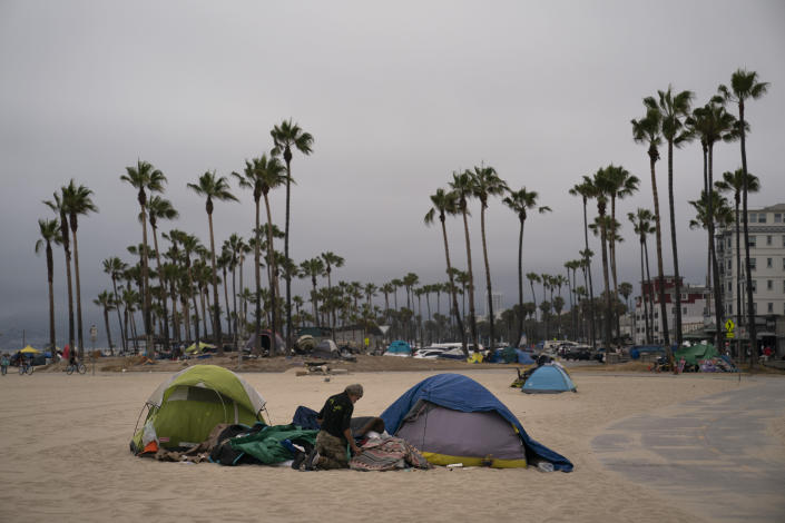 A homeless man goes through his belongings outside his tent pitched on the beach in the Venice neighborhood of Los Angeles, Tuesday, June 29, 2021. The proliferation of homeless encampments on Venice Beach has sparked an outcry from residents and created a political spat among Los Angeles leaders. (AP Photo/Jae C. Hong)