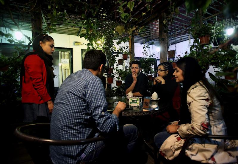 """In this Tuesday, March 4, 2014 photo, young Iranian adults sit at a cafe in Tehran, Iran. For years Iranian authorities kept the number of cafes limited since they were seen as a symbol of Western influence and places to spread non-Islamic beliefs. But reports of cafes being shut because they violate """"Islamic dignities"""" have dropped markedly in recent months, suggesting a growing tolerance by the authorities. (AP Photo/Vahid Salemi)"""